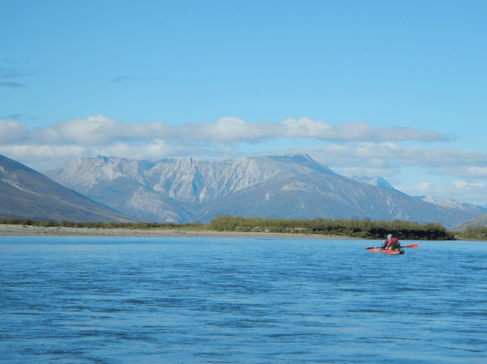Ice covered mountains behind a cool blue river with kayaker