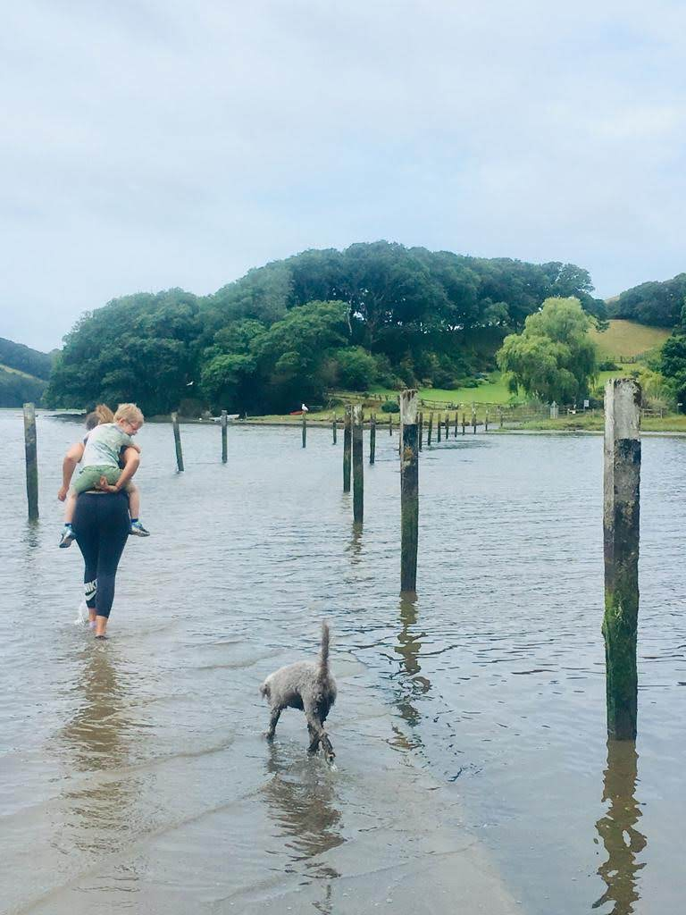 With a child on her pack and a dog at her heels, a woman makes her way across a river on a flooded boardwalk.
