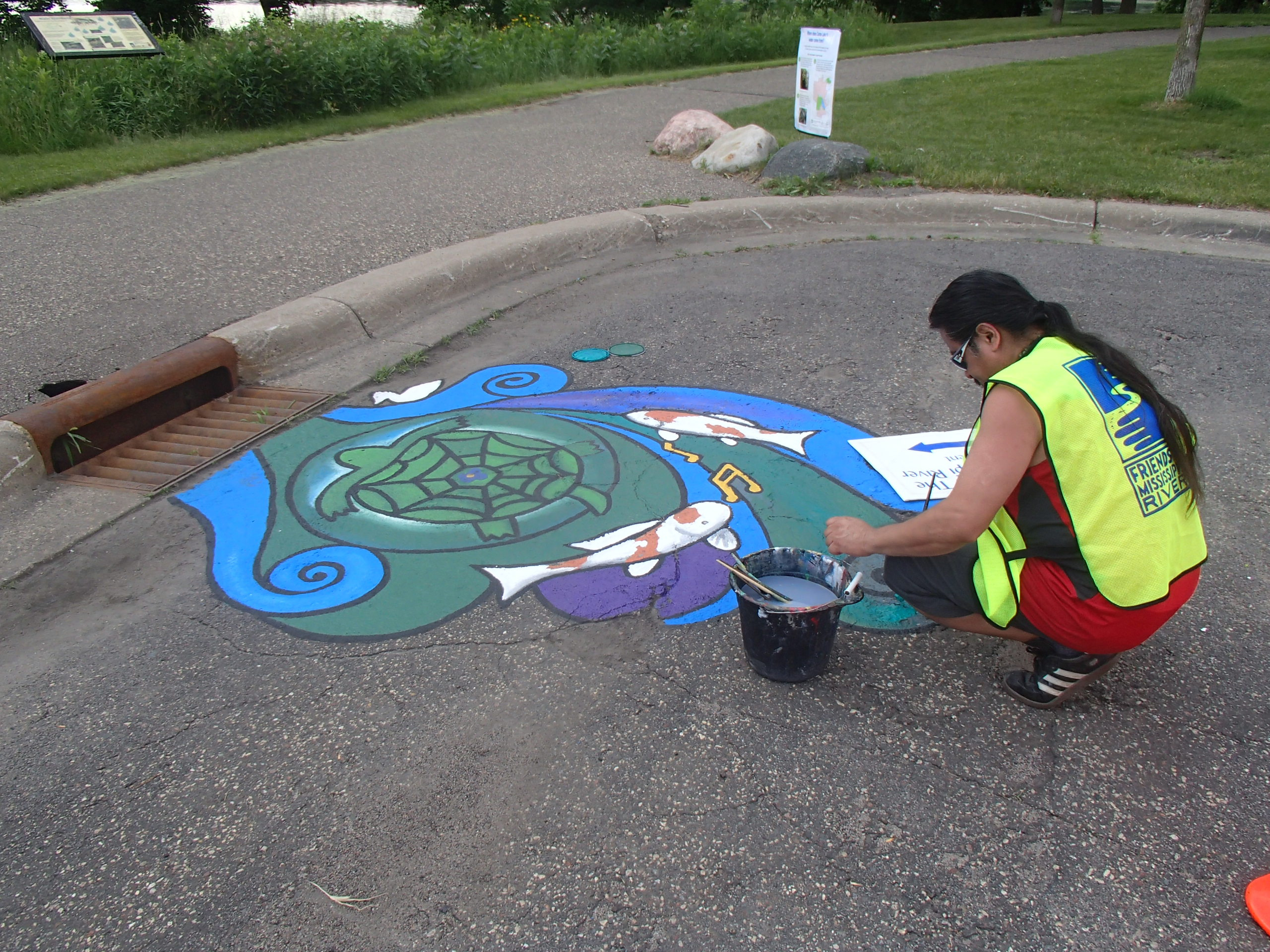 FMR's first storm drain mural depicting a snapping turtle, koi fish and musical notes