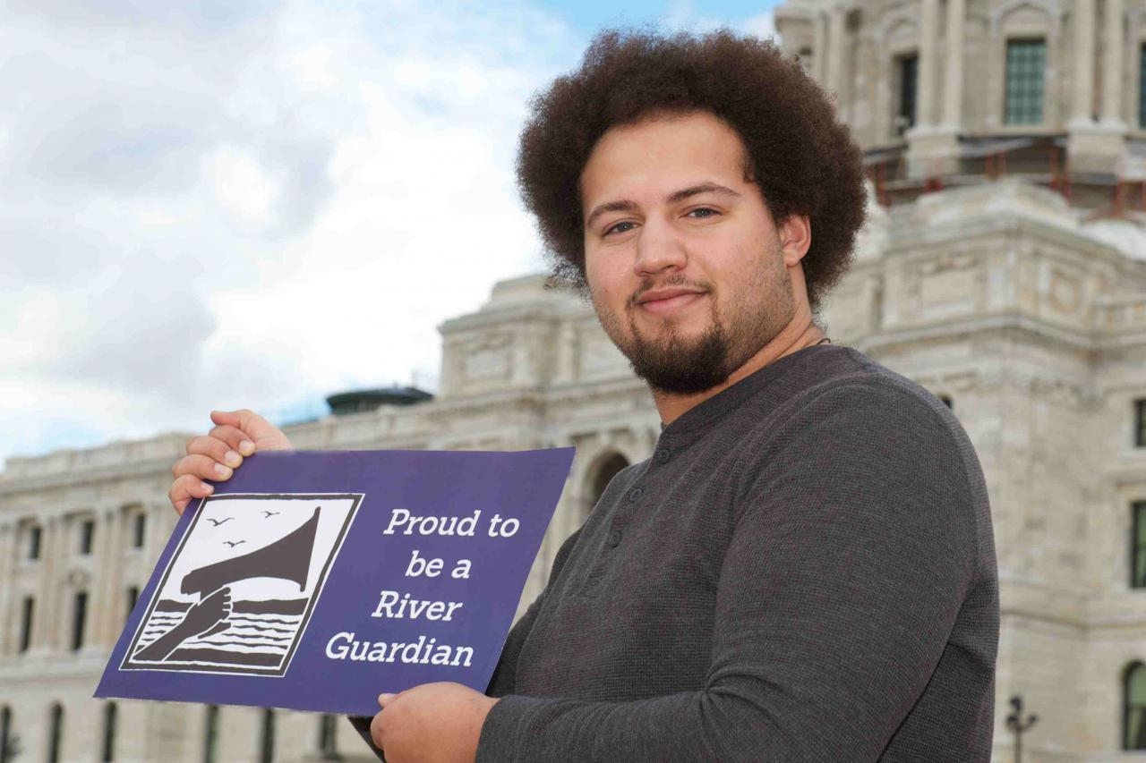 "A man stands in front of the MN state capitol with a sign reading ""proud to be a river guardian"""