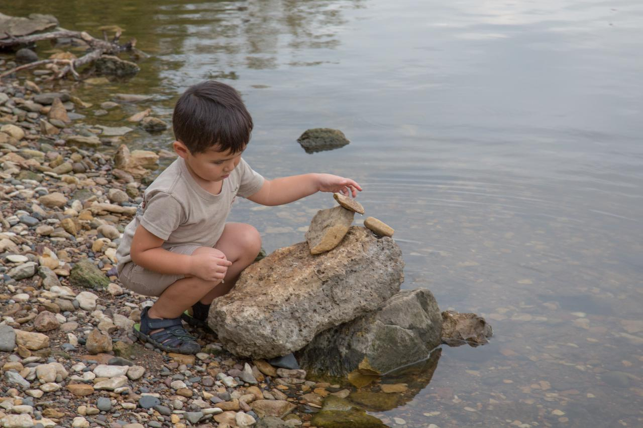 Young child is playing with rocks along the bank of the Mississippi River
