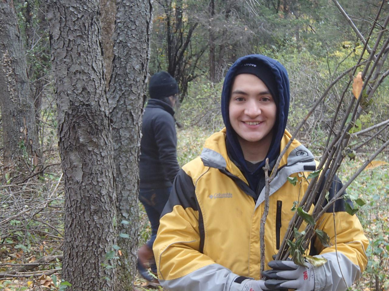 A volunteer poses with buckthorn sticks at a past Ravine Park brush haul