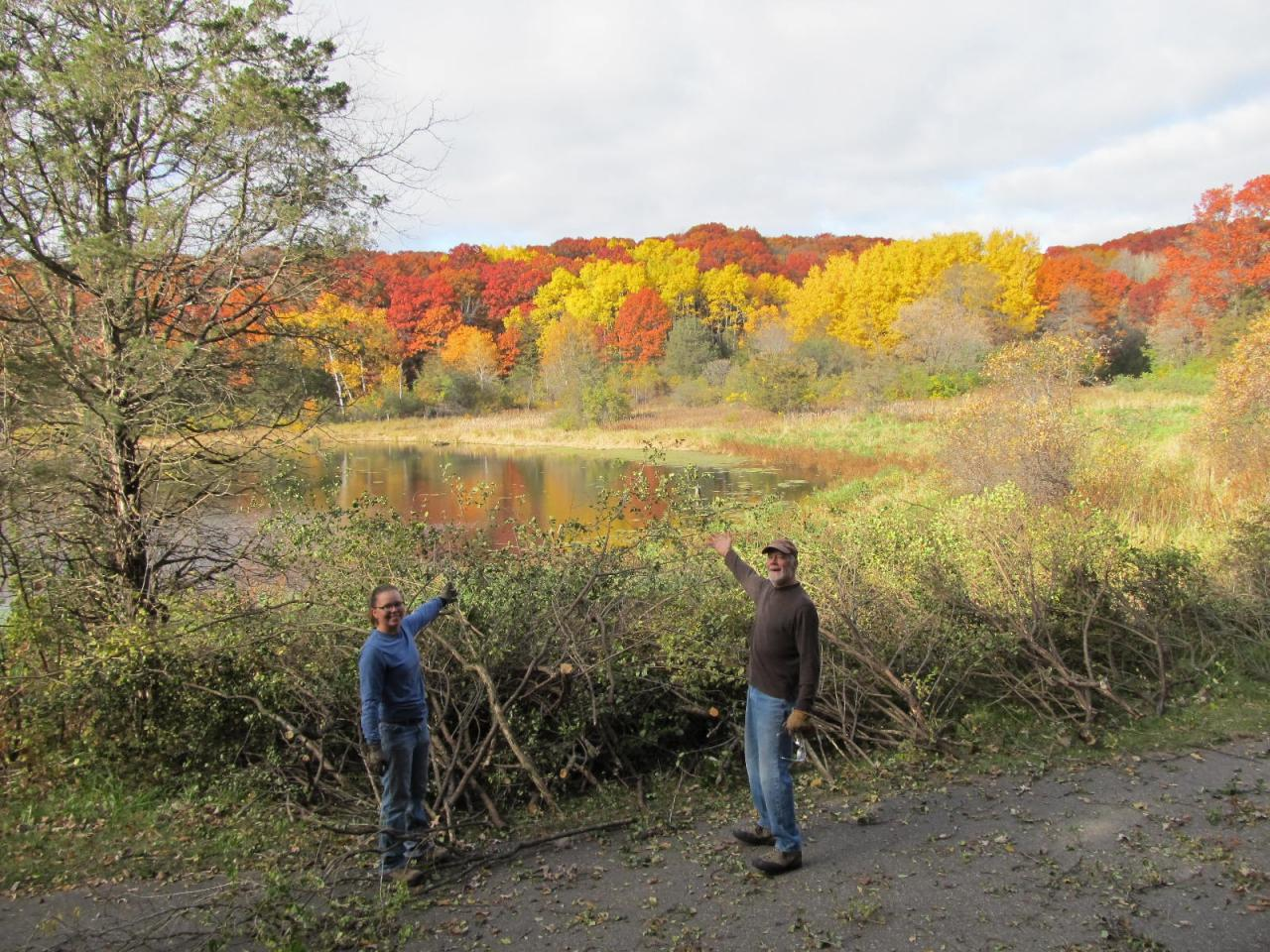 Not a bad view at all! Volunteers pose in front of their hauled brush pile along the edge of the lake.
