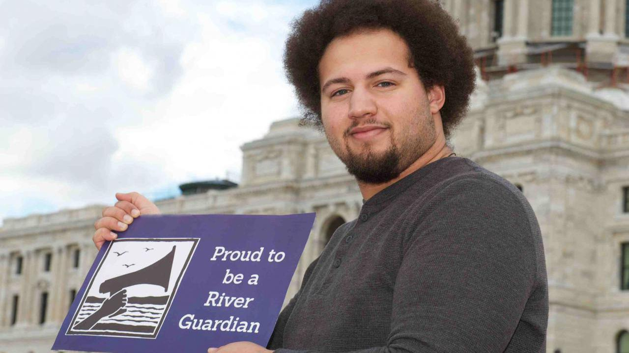 """A man stands in front of the MN state capitol with a sign reading """"proud to be a river guardian"""""""