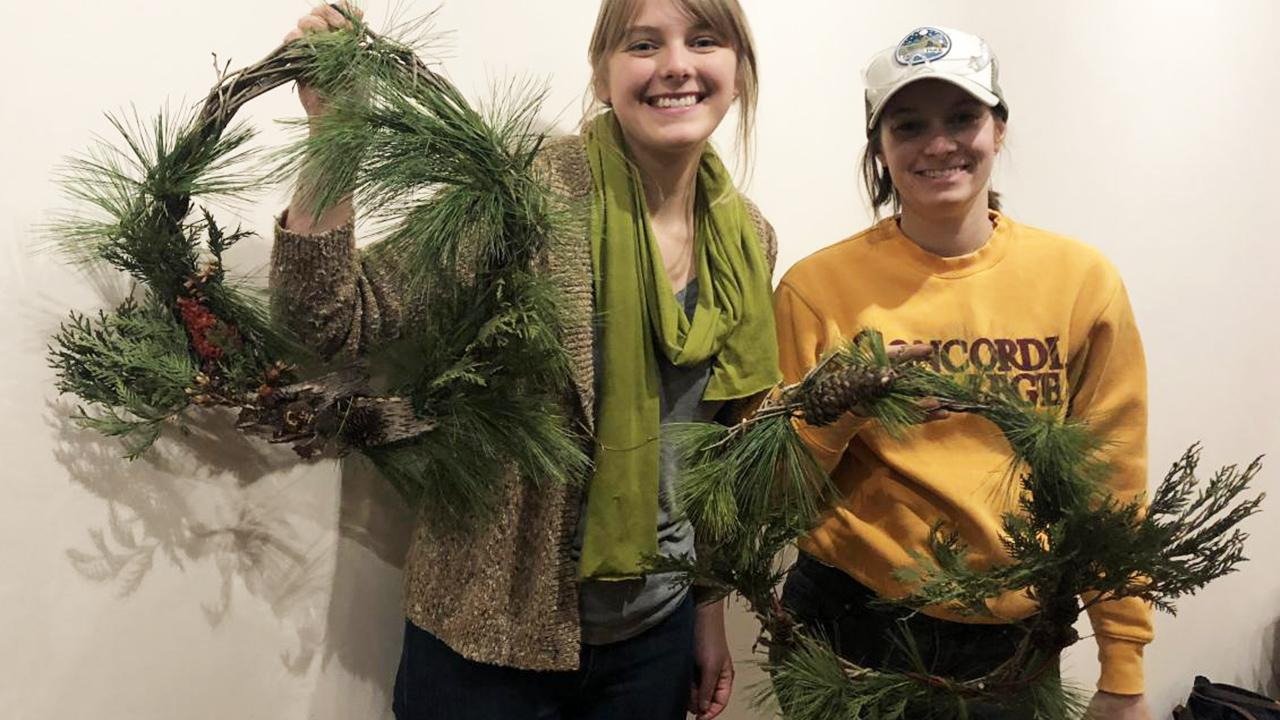 Two workshop participants display their buckthorn wreath creations.