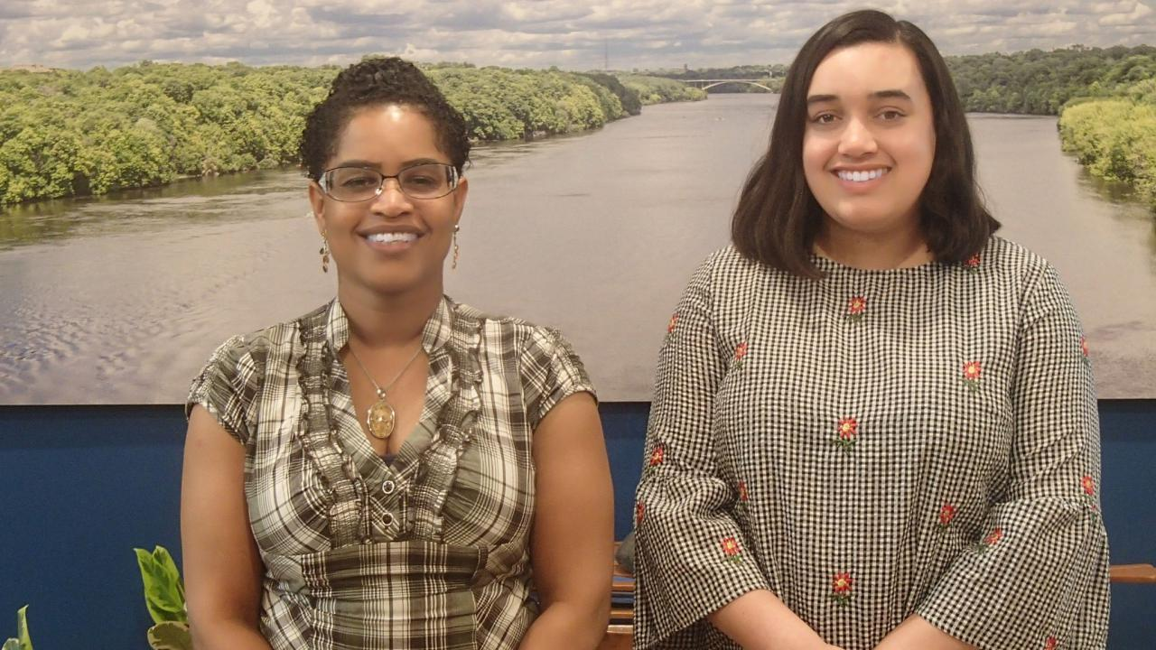 Raynette Prince and Sophie Downey stand before a large photo of the Mighty Mississippi.