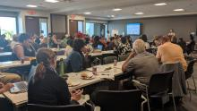 About 70 people sit at tables in a meeting room, facing a presenter.
