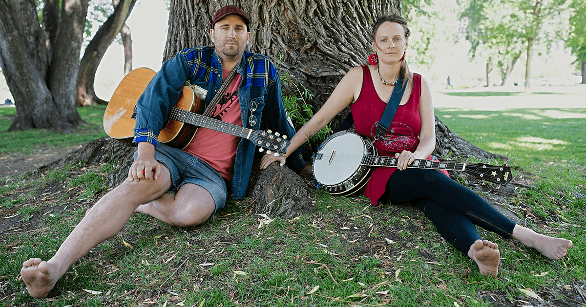 Two musicians sit by a tree